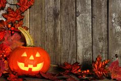 Halloween Jack o Lantern with an autumn leaves corner border on wood. Halloween Jack o Lantern with corner border of autumn leaves on a rustic wooden background Royalty Free Stock Photography