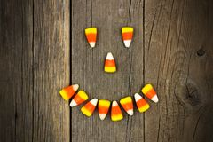 Halloween Jack o Lantern face of candy corn over wood Stock Photo