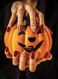 Halloween jack o lantern and manicure with gems and sequins. Nail art concept. Pumpkin in female hands on black background. Holiday and party celebration stock photo