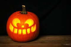 Halloween Jack o Lantern on old wood with black background Royalty Free Stock Images
