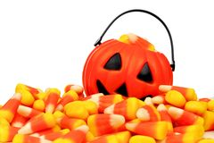 Halloween Jack-o-Lantern pail behind pile of candy corn over white Royalty Free Stock Image