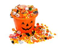 Halloween Jack o Lantern pail overflowing with candy. Halloween Jack o Lantern candy pail overflowing with assorted sweets over a white background royalty free stock photography