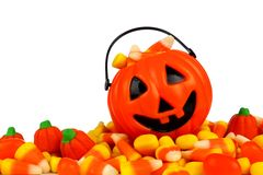 Halloween Jack-o-Lantern pail on a pile of candy over white Stock Photos