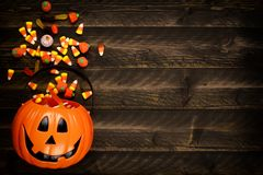 Halloween Jack o Lantern pail with side border of spilling candy over dark wood. Halloween Jack o Lantern pail with side border of spilling candy. Above view on royalty free stock photo