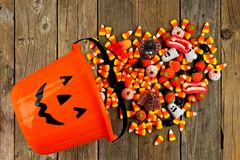 Halloween Jack o Lantern pail with spilling candy over wood Royalty Free Stock Photos