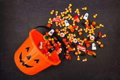 Halloween Jack o Lantern pail, top view with spilling candy. Halloween Jack o Lantern pail with spilling candy, above view on a dark background stock photo