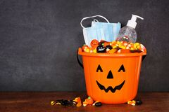 Free Halloween Jack O Lantern Pail With Candy And Coronavirus Prevention Supplies Against A Dark Background Royalty Free Stock Images - 196073589
