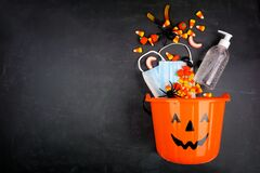 Free Halloween Jack O Lantern Pail With Spilling Candy And COVID 19 Prevention Supplies Over A Black Background Stock Photo - 196073670