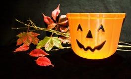 Halloween Jack-O-Lantern pumpkin. Celebrating Halloween night with pumpkin Jack-O-Lantern basket and autumn leaves Royalty Free Stock Image