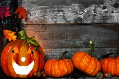 Halloween Jack-o-Lantern and pumpkin corner border against rustic wood Royalty Free Stock Photography