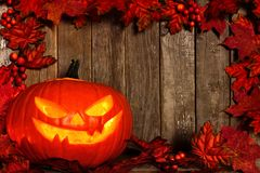 Halloween Jack o Lantern with an autumn leaves frame on wood Stock Photography