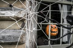 Halloween Jack O Lantern In Window. Halloween Background. Jack O Lantern and spider web decorations on exterior wall of home royalty free stock photo