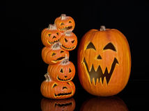 Halloween Jack O Lanterns. Already carved and sitting on a table.  One large pumpkin and one stack of 6 small pumpkins Royalty Free Stock Image