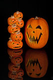 Halloween Jack O Lanterns. Already carved and sitting on a table.  One large pumpkin and one stack of 6 small pumpkins Stock Image