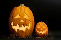 Halloween Jack-O-Lanterns. One large and one small lighted and smiling Halloween jack-o-lanterns with fall leaves underneath and black background Royalty Free Stock Photo