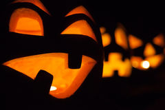Halloween jack-o-lanterns. Spooky halloween jack-o-lanterns with lit candles glowing behind carved faces Stock Image