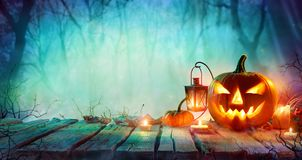 Halloween - Jack O` Lanterns And Candles On Table. In Misty Night Stock Image