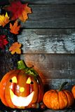 Halloween Jack-oLantern with pumpkin corner border against rustic wood Stock Image