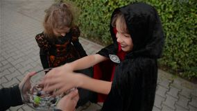 Halloween, Jonge geitjes wil Halloween-Suikergoed, Kinderen die heksenkostuums met hoeden, Jonge geitjestruc dragen of behandelt stock footage
