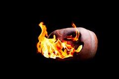 Halloween-Kürbis auf dem Feuer lokalisiert auf einem schwarzen Hintergrund Lizenzfreies Stockbild