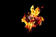 Halloween-Kürbis auf dem Feuer lokalisiert auf einem schwarzen Hintergrund Lizenzfreie Stockbilder