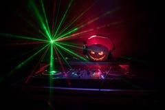 Halloween-Kürbis auf einer DJ-Tabelle mit Kopfhörern auf dunklem Hintergrund mit Kopienraum Glückliche Halloween-Festivaldekorati lizenzfreies stockbild