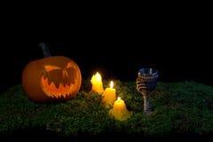 Halloween-Kürbis, -becher und -kerzen, die in die Dunkelheit auf einem f glühen Lizenzfreies Stockfoto