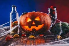 Halloween-Kürbis in einem Spinnennetz mit Bonbons und dunkler Beleuchtung Süßes sonst gibt's Saures Konzept auf blauem und rotem  Stockfotos