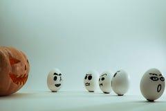 Halloween-Kürbis gegen verärgerte Eier Stockbilder