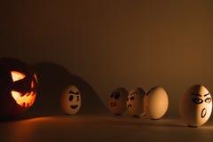 Halloween-Kürbis gegen verärgerte Eier Lizenzfreie Stockfotos