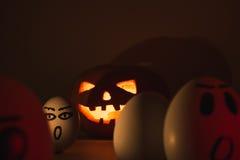 Halloween-Kürbis gegen verärgerte Eier Stockfotografie