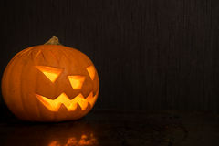 Halloween-Kürbis mit der Feuerkerze, die auf dunklen Hintergrund mit glüht Stockbild