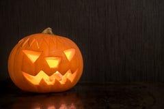 Halloween-Kürbis mit der Feuerkerze, die auf dunklen Hintergrund mit glüht Lizenzfreies Stockfoto