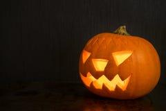 Halloween-Kürbis mit der Feuerkerze, die auf dunklen Hintergrund mit glüht Stockfotos