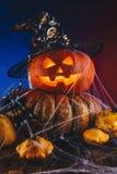 Halloween-Kürbis mit Hut in einem Spinnennetz mit Bonbons und dunkler Beleuchtung Süßes sonst gibt's Saures Konzept auf Blauem un Lizenzfreie Stockfotografie