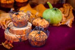 Halloween-Kürbis-Muffins verziert mit Spinnen und Spinnen-Netz Lizenzfreies Stockfoto