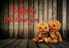 Halloween-Kürbise auf hölzernem Hintergrund mit Mitteilung u. x27; Glückliches Halloween& x27; Stockbild