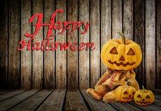 Halloween-Kürbise auf hölzernem Hintergrund mit Mitteilung u. x27; Glückliches Halloween& x27; Lizenzfreies Stockfoto