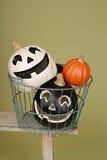 Halloween-Kürbise auf rustikaler hölzerner Bank in der Draht-Schüssel Lizenzfreie Stockbilder