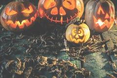 Halloween-Kürbise am hölzernen Hintergrund Geschnitzte furchtsame Gesichter des Kürbises Lizenzfreies Stockbild