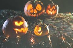 Halloween-Kürbise am hölzernen Hintergrund Geschnitzte furchtsame Gesichter des Kürbises Lizenzfreies Stockfoto