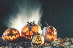 Halloween-Kürbise am hölzernen Hintergrund Geschnitzte furchtsame Gesichter des Kürbises Stockbild