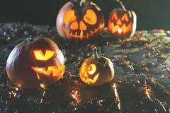 Halloween-Kürbise am hölzernen Hintergrund Geschnitzte furchtsame Gesichter des Kürbises Stockbilder