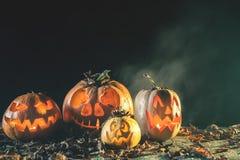Halloween-Kürbise am hölzernen Hintergrund Geschnitzte furchtsame Gesichter des Kürbises Stockfoto