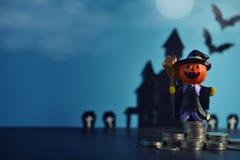 Halloween-Kürbissteckfassung-olaterne mit wachsendem Geschäft des Geldmünzen-Stapels auf dunkelblauem Hintergrund Stockbilder