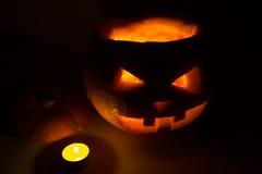 Halloween-Kürbissteckfassungslaterne mit Kerze auf Dunkelheit Stockbilder