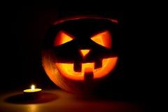 Halloween-Kürbissteckfassungslaterne mit Kerze auf Dunkelheit Stockfotos