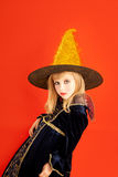 Halloween kid girl costume on orange. Background stock photo