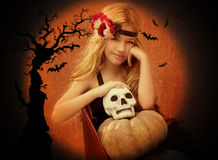 Halloween kid girl with pumpkin and skull smiling Royalty Free Stock Photo
