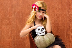 Halloween kid girl with pumpkin and skull smiling Stock Image